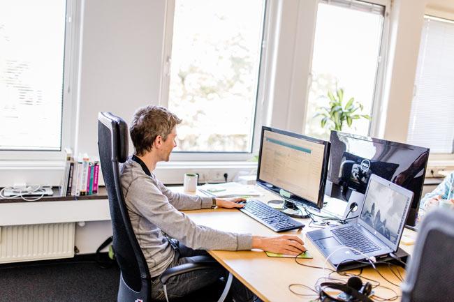 Mitarbeiter Boris an seinem Arbeitsplatz mit 28 Zoll 4K Bildschirm und modernem Laptop
